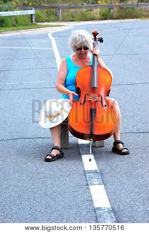 Mature female cellist performing in the street outdoors.