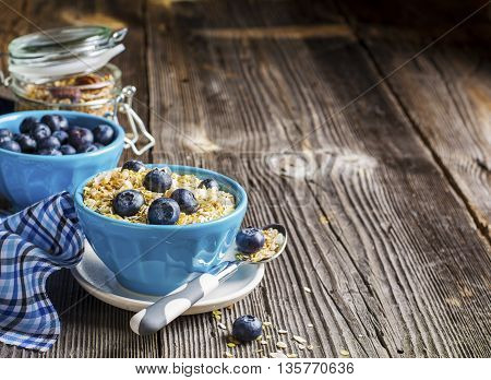 Healthy breakfast. Multigrain Flakes of 4 kinds of grain, fresh forest blueberries in blue ceramic bowls portsinno breakfast. The concept of useful natural home power