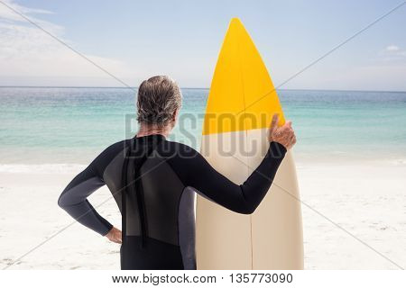 Rear view of senior man in wetsuit holding a surfboard on the beach