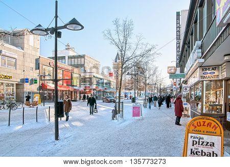 LAPPEENRANTA, FINLAND - FEBRUARY 18, 2010: People walk along store buildings on the Oleksi pedestrian zone - part of the Kauppakatu Street. Winter period