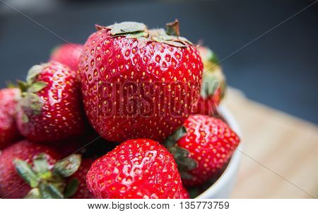 Freshly harvested strawberries in a white dish