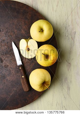 Golden Delicious apple still life with knife. Dark round surface on rustic table.