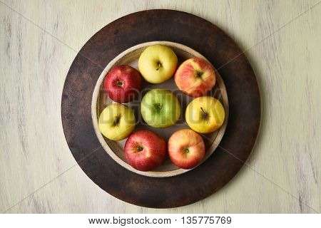 High angle view of a bowl of assorted apples on a rustic table.
