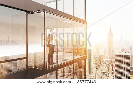 Thoughtful businessman looking into the distance from empty balcony interior on New York city background with sunlight. 3D Rendering