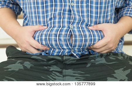 Fat belly . Man with overweight abdomen .