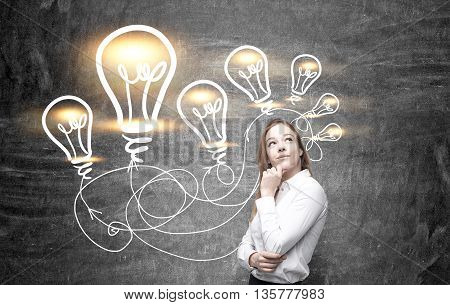 Idea concept with thoughtful businesswoman and illuminated lightbulb sketches on chalkboard background