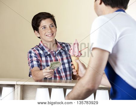 Boy Paying For Strawberry Ice Cream To Waiter At Shop