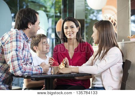 Family Looking At Mother In Ice Cream Parlor