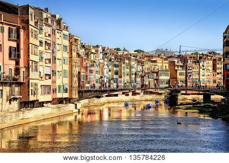 GIRONA SPAIN - MAY 10 2015: Flowers and house's reflection in Onyar River during Festival of floral decorations in Girona Catalonia Spain