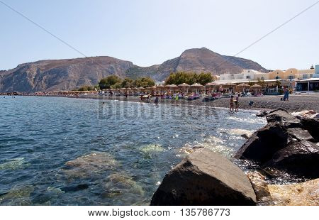 SANTORINIFIRA-JULY 28: Tourists sunbathe on the Kamari Beach on July 282014 on the island of Santorini(Thira) Greece. Kamari beach is located on the eastern coast of Santorini Island.