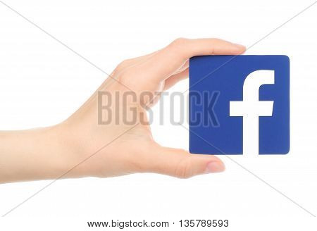 Kiev Ukraine - May 18 2016: Hand holds facebook logo printed on paper on white background. Facebook is a well-known social networking service.