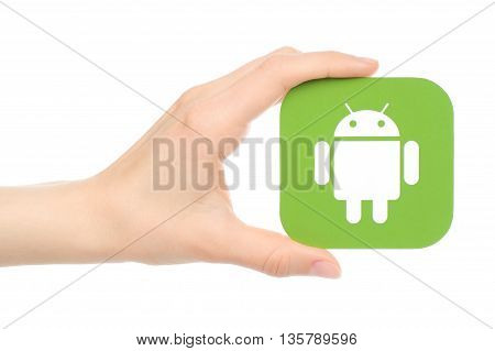 Kiev Ukraine - May 18 2016: Hand holds Android logo printed on paper on white background.