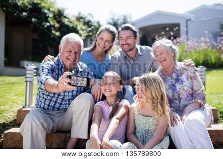 Multi-generation family taking a selfie in the garden on a sunny day