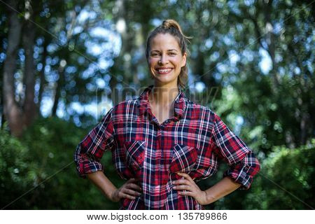 Portrait of confident woman with hands on hip standing in back yard