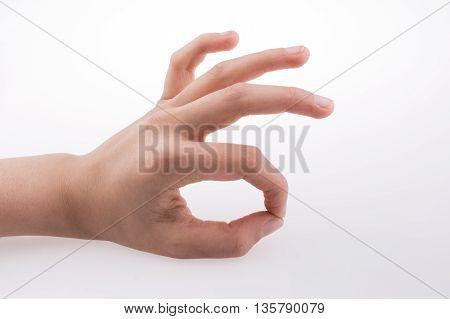 Hand making 'good' symbol on a whitebackground