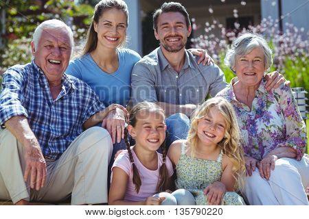 Portrait of happy family sitting in back yard