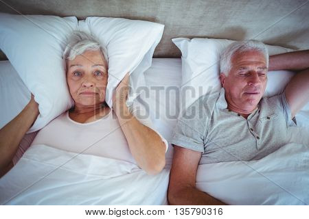 Annoyed wife blocking ears with pillow while husband snoring on bed