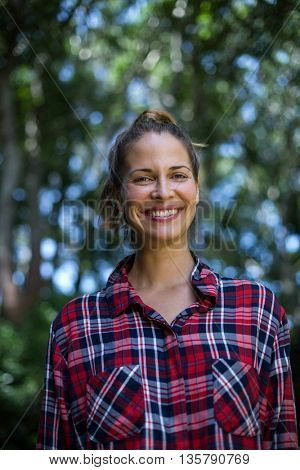 Portrait of confident young woman while standing in back yard