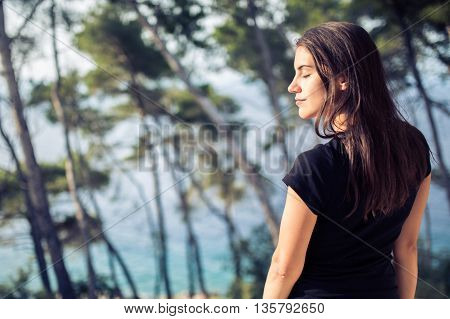 Beautiful woman enjoying the sea view from the balcony.Pinewood and sea background.Enjoying perfect holiday.Summer vacation.