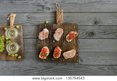 Wine with appetizers for wine and grapes. Sandwich with tomatoes goat cheese and ham on a wooden board on a dark surface. Rustic style top view