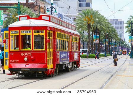 NEW ORLEANS, USA - MAY 14, 2015: Red streetcar on Canal Street in the back another streetcar approaching and people crossing the street.