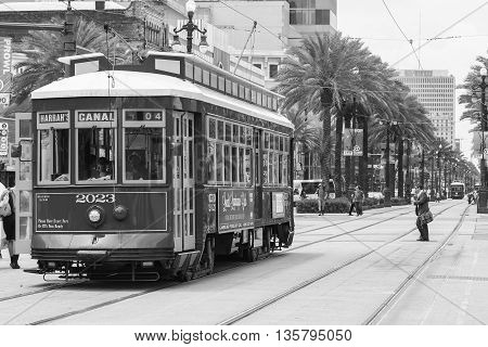 NEW ORLEANS, USA - MAY 14, 2015: Streetcar on Canal Street in the back another streetcar approaching and people crossing the street.