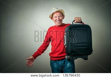 portrait of the funny senior man with travel bag