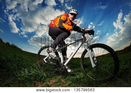Young man riding on bicycle through deep grass with red backpack against blue sky