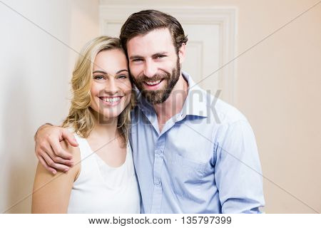Portrait of happy couple standing with arm around at home