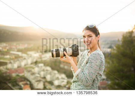 Female traveler photographer smiling,loving her job.Professional photographer taking outdoor portraits with telephoto lens.Taking photos of animals in the nature.See sight on hilltop above town.