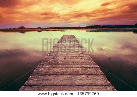 Old Wooden Pier At Colorful Sunset Sunrise. Calm River Nature Background. Toned Instant Filtered Photo Image