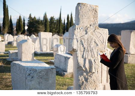 Radimlja necropolis in Bosnia and Hercegovina.Stecak tombstones from mediaeval period.Ancient european cemetery.Archeologist working