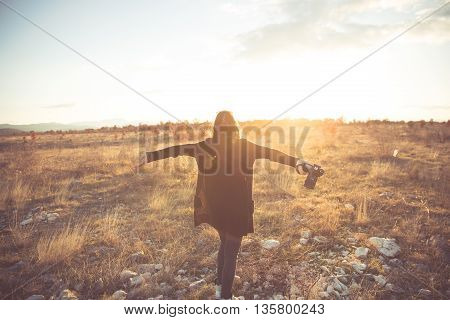 Carefree happy woman enjoying sun on her face and photographing sunset raising hands in sunlight rays,enjoying nature sunset.Freedom.Enjoyment.Relaxing in meadow at sunrise.Daydreaming