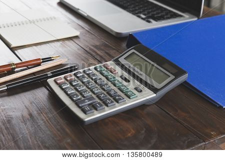 Calculator, Laptop Computer, Pen And Notebook On Office Desk