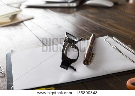 eyeglasses pen and notepad on wooden office desk