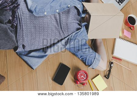 Woman Lying On Floor With Mobile Phone, Notebook And Laptop