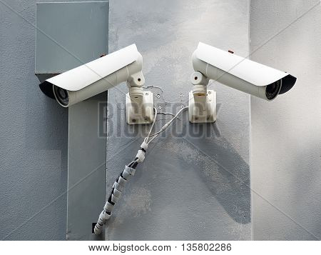 White CCTV (Closed circuit TV) camera security monitoring on cement wall.