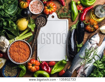 Ingredients for cooking healthy dinner. Raw uncooked seabass fish with vegetables, grains, herbs and spices over rustic wooden background, white ceramic board in center with copy space, square crop. Top view