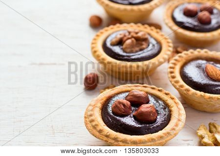 Nutty chocolate dessert small tarts on a white background, space for text