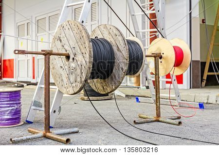 Cable spool is on the axle until worker unwinds wire.