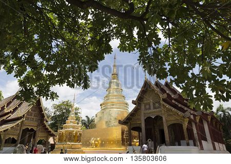 Golden Pagoda And Sanctuary In Buddhism Temple With Leaves Frame