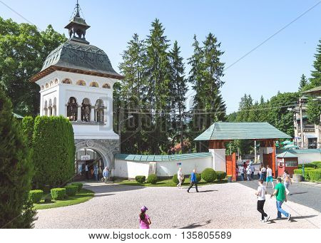 Sinaia, ROMANIA - June 18 2016: The bell tower of Sinaia monastery and the yard filled with tourists. SINAIA - June 18 2016