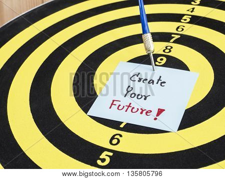 Handwriting Create your future on notepaper with dart arrow and dart board. (Business concept)