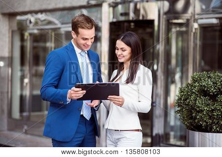 Involved in project. Pleasant professional delighted colleagues holding folder and talking while standing near office building