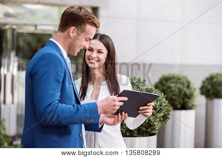 Discuss business affairs. Pleasant cheerful smiling colleagues standing near office building and holding tablet while talking