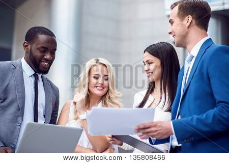 Glad to work together. Cheerful delighted smiling colleagues standing near office building and discussing project while expressing gladness