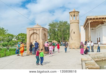 BUKHARA UZBEKISTAN - APRIL 29 2015: The minaret of Khakim Kushbegi Mosque is neighboring with the modern ablution fountain on April 29 in Bukhara.