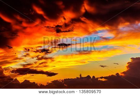 Amazing sunset sky background, red dramatic cloudscape, overcast weather, sun down, dreamy evening