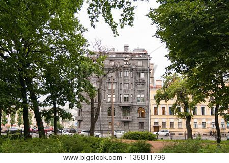Dark gray eclectic house on Avenue of Rimsky-Korsakov in St. Petersburg. View from the garden Nikolsky.