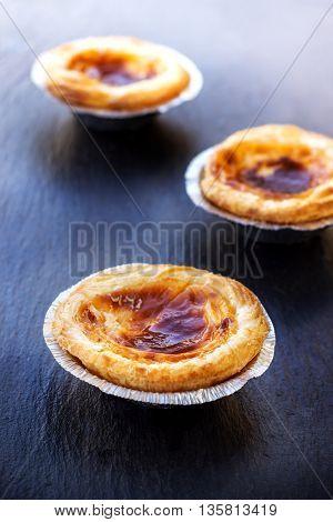 Egg tart on a grunge background, traditional portuguese dessert, pasteis de nata. Selective focus